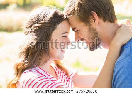 Cute coupe smiling at each other in park on a sunny day - stock photo