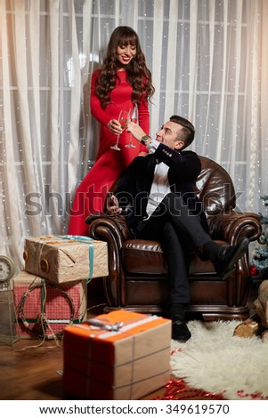 Cute couple celebrate Christmas with champagne - stock photo