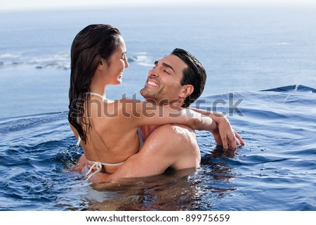 Cute couple cuddling each other in a swimming pool - stock photo