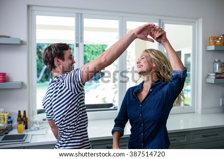 Cute couple dancing in the kitchen - stock photo