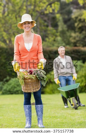 Cute couple doing some gardening in the garden - stock photo
