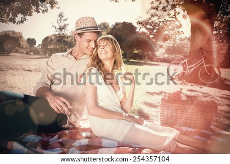 Cute couple drinking white wine on a picnic smiling at each other on a sunny day - stock photo