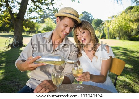 Cute couple drinking white wine together outside on a sunny day - stock photo