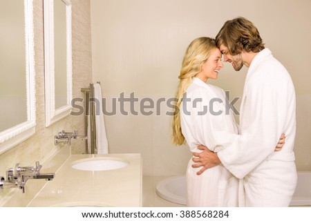 Cute couple embracing in bath robe in the bathroom at home - stock photo