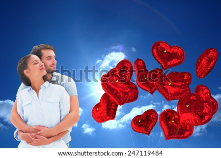 Cute couple embracing with eyes closed against sky - stock photo