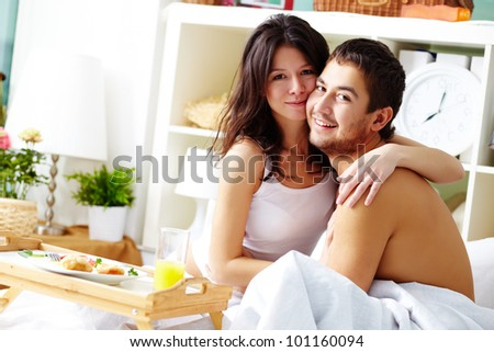 Cute couple enjoying a morning together having breakfast in bed - stock photo