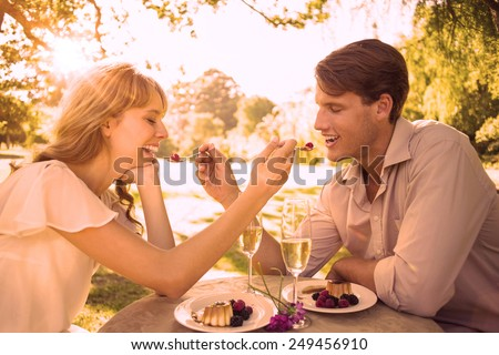 Cute couple feeding each other dessert on a sunny day - stock photo