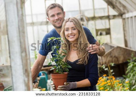 Cute couple gardening in greenhouse at home in the garden - stock photo
