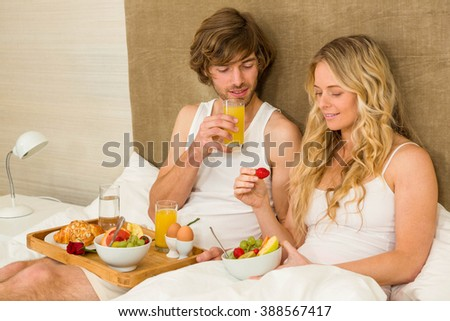 Cute couple having breakfast in bed in the bedroom