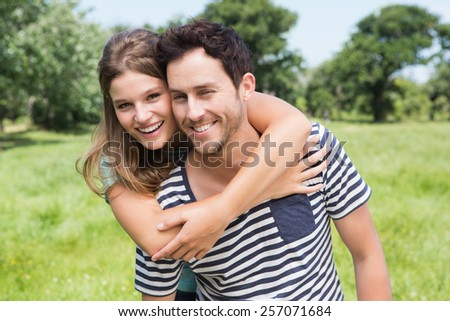 Cute couple having fun in park on a sunny day - stock photo