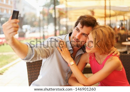 Cute couple having fun in the cafe taking self portrait with mobile phone. - stock photo