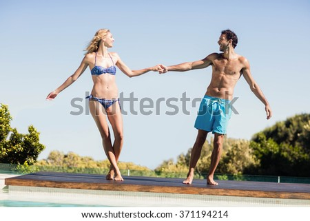 Cute couple holding hands by the pool - stock photo
