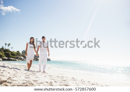 Cute couple holding hands on the beach