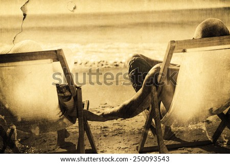 Cute couple holding hands while lying on their deck chairs against grey background