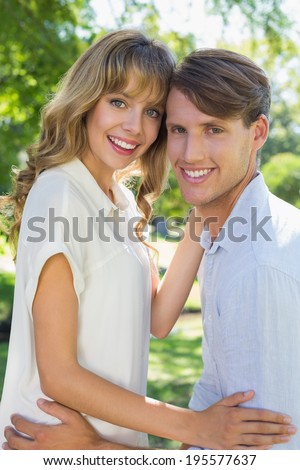 Cute couple hugging and smiling at camera in the park on a sunny day