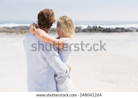Cute couple hugging on the beach on a sunny day - stock photo
