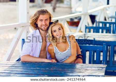 Cute couple in love hugging and smiling sitting at table in cozy cafe on the beach. - stock photo