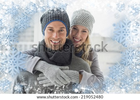 Cute couple in warm clothing hugging smiling at camera against snow - stock photo