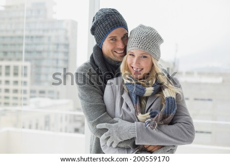 Cute couple in warm clothing smiling at camera on a chilly day - stock photo