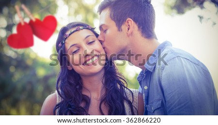 Cute couple kissing in the park against hearts hanging on a line - stock photo