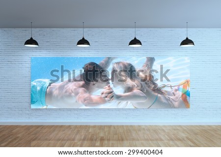 Cute couple kissing underwater in the swimming pool against room with poster display - stock photo