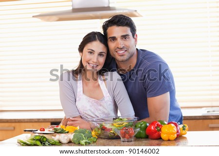 Cute couple looking at the camera in their kitchen
