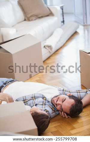 Cute couple lying on the floor in their new home - stock photo