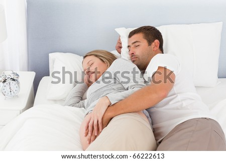 Cute couple of future parents doing a nap in the bedroom - stock photo