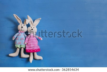 Cute couple of handmade sewed easter bunny on blue wooden background for decoration. - stock photo