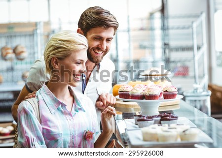 Cute couple on a date looking at cakes at the bakery - stock photo