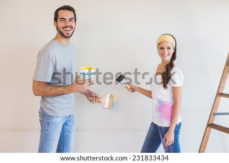 Cute couple painting the wall in their new home - stock photo