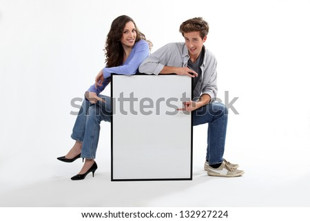 cute couple pointing at copyspace - stock photo