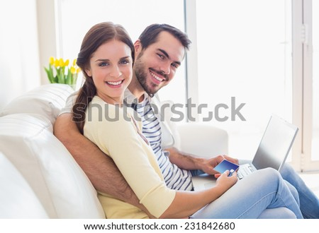 Cute couple relaxing on couch with laptop at home in the living room - stock photo