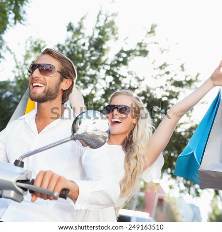 Cute couple riding a scooter on a sunny day in the city - stock photo