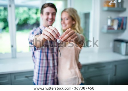 Cute couple showing their new home keys in the kitchen - stock photo
