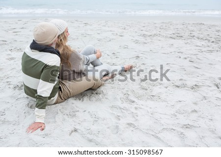 Cute couple sitting in the sand at the beach