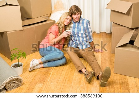 Cute couple sitting on the floor while drinking in their new house - stock photo
