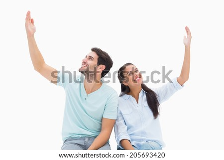 Cute couple sitting with arms raised on white background - stock photo
