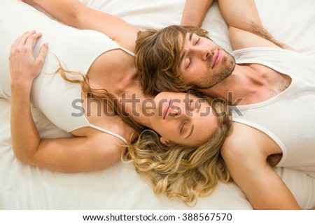 Cute couple sleeping on their bed in the bedroom - stock photo