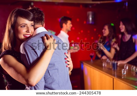 Cute couple slow dancing together at the nightclub - stock photo