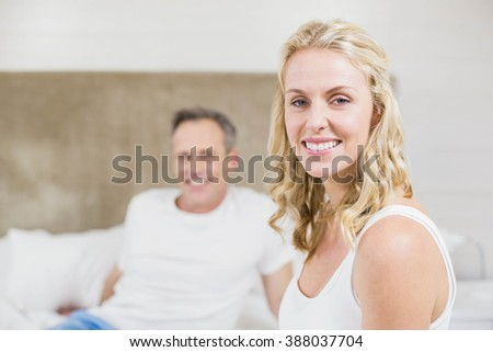 Cute couple smiling at camera in bed