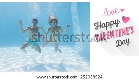 Cute couple smiling at camera underwater in the swimming pool against cute valentines message - stock photo