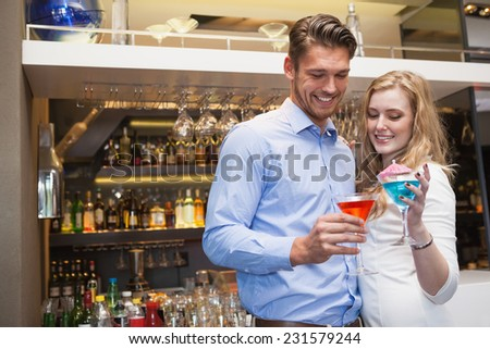 Cute couple standing and drinking cocktails at the night club