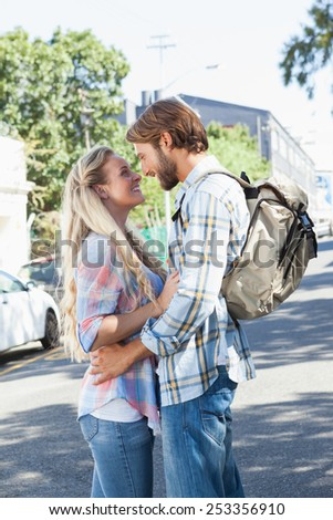 Cute couple standing and hugging on a sunny day in the city - stock photo