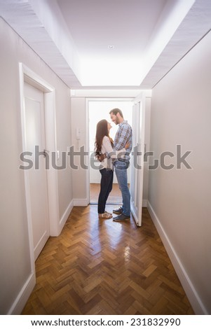 Cute couple standing in the hall in their new home - stock photo