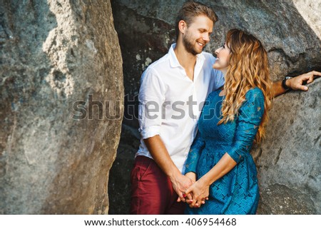 Cute couple standing together near rocks, outdoor. Profile. Girl wearing blue dress and man wearing white shirt and claret trousers, he has stylish haircut - stock photo