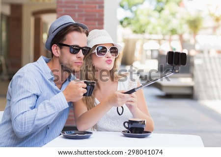 Cute couple taking a selfie while doing funny faces - stock photo