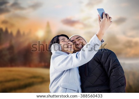 Cute couple taking selfie against country scene