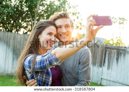 Cute couple taking selfies together - stock photo