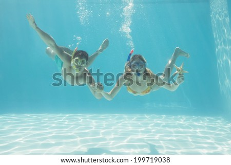 Cute couple underwater in the swimming pool with snorkel and starfish on their holidays - stock photo